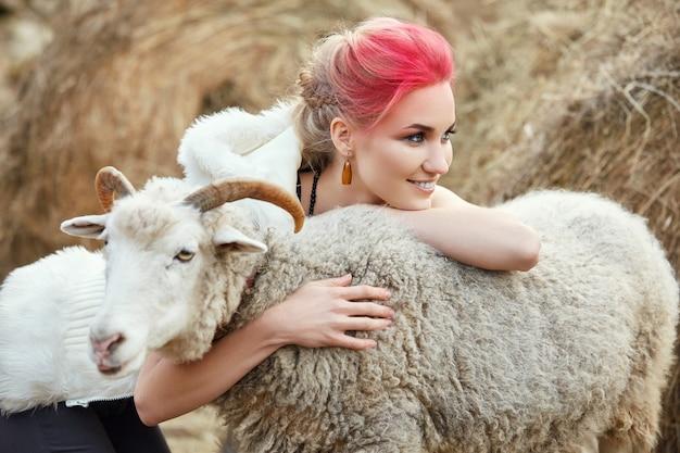 Женщина ярко-красный макияж на лице обнимает рогатый баран. креативный ярко-розовый макияж на лице девушки, окраска волос. портрет девушки с овцой. прогулка по осеннему лесу. осенняя шерстяная одежда