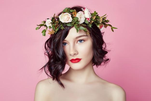 女性の明るい夏の花の花輪を頭に