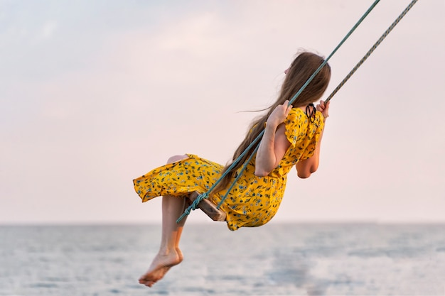 Woman in bright yellow dress rides on swing against the sea background. alone with thoughts. loneliness.