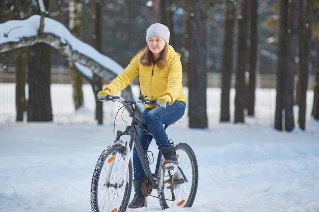 Woman in a bright yellow jacket rides a bicycle in winter in the snow.