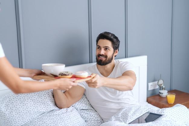 Женщина приносит завтрак своему любящему мужу. человек сидит в постели и принимает поднос. Premium Фотографии