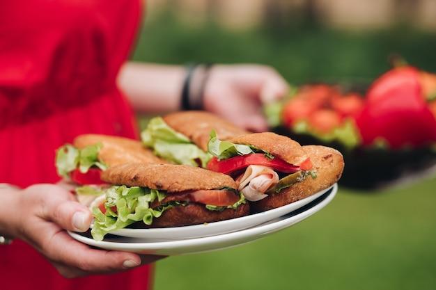 신선한 샌드위치를 가져오는 여자. 접시에 맛있는 수제 샌드위치를 들고 있는 알아볼 수 없는 여성의 클로즈업. 빵, 토마토, 샐러드, 돼지고기.
