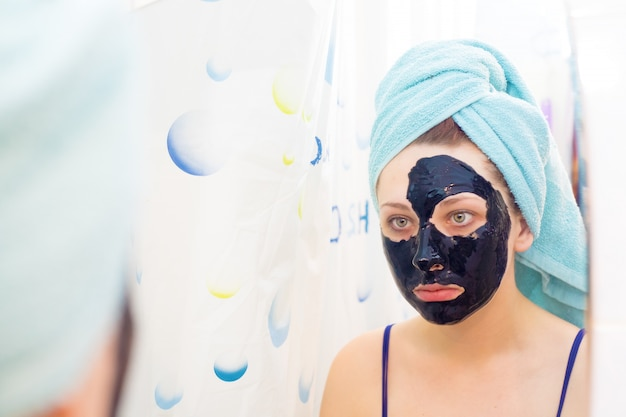 Woman brings beauty to her face, gets rid of black dots, using a black mask