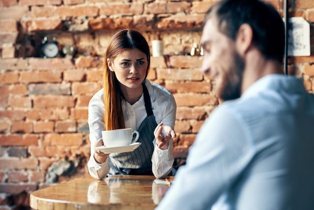 Woman brings coffee to customer waiter work service