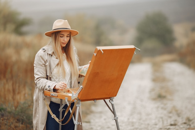 Woman in a brown coat painting in a field