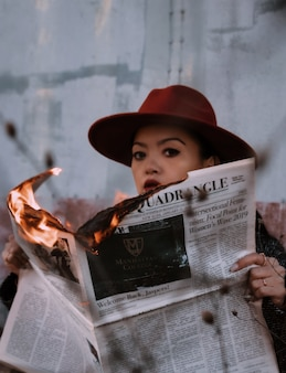 Woman in brown hat holding burning newspaper