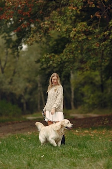Woman in a brown sweater. lady with a labrador. friends are having fun outside.