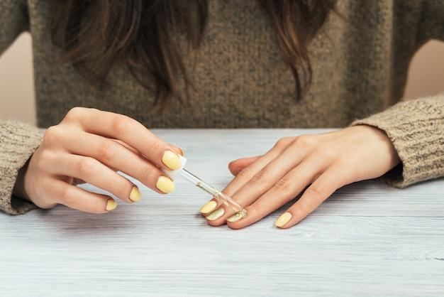 Woman in a brown sweater with yellow manicure applying cosmetic oil on the skin, close-up