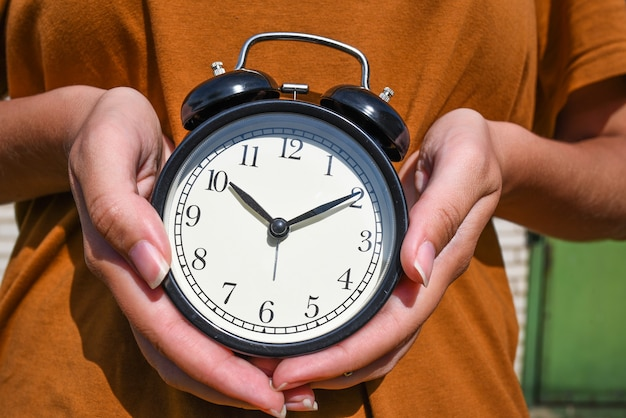 Woman in brown t-shirt holding alarm clock in hand.