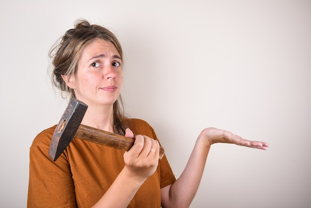 Woman in brown t-shirt, holding hammer, looking at camera, isolated on white wall. home renovation concept