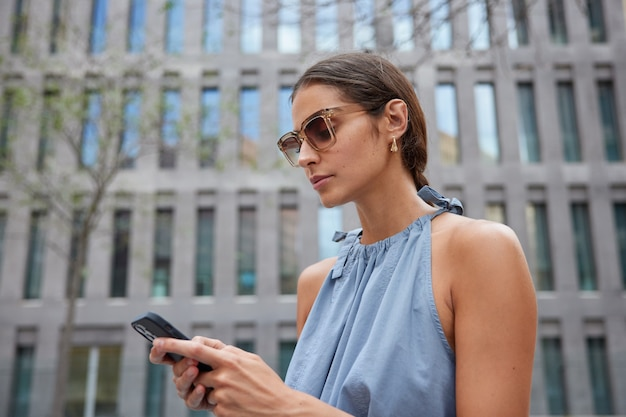 Woman browses mobile phone stands near modern building wears stylish sunglasses blue dress strolls across touristic street messages via cellular