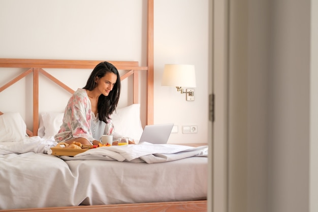 Woman browsing laptop in bed in morning