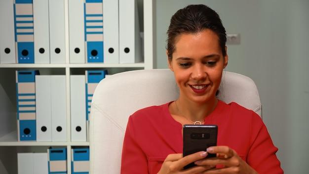 Женщина, просматривающая смартфон, улыбаясь, сидя на столе в современном офисе. латиноамериканский предприниматель, работающий на профессиональном рабочем месте в корпоративной компании, печатает на мобильном телефоне перед компьютером
