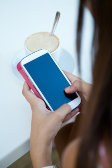 Woman browsing phone while drinking coffee