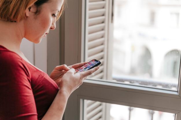 Woman browsing smartphone near window