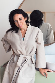 Woman brunette in cotton bathrobe posing at bathroom look at camera selfcare concept