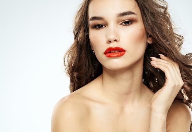 まぶたの肖像画の裸の肩に女性ブルネットの赤い唇の影