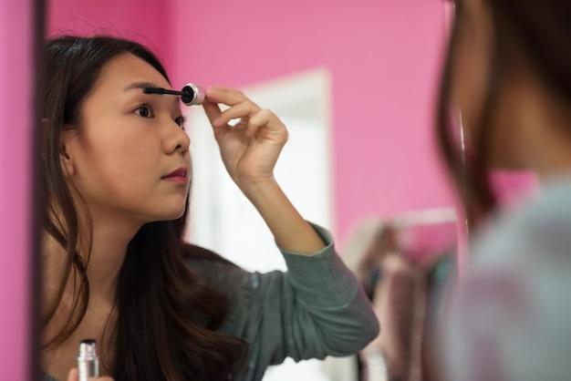 Woman brush eyelashes at mirror