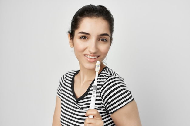 Woman brush your teeth with a toothbrush isolated background