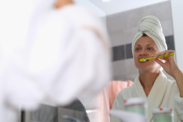 Woman brushes teeth in front of mirror closeup