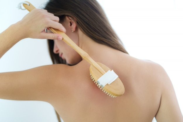 Woman brushing back with a dry wooden brush to prevent and treatment body problem after shower at home. skin health