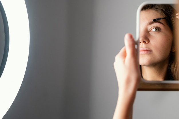 Женщина расчесывает брови, глядя в зеркало после процедуры с копией пространства