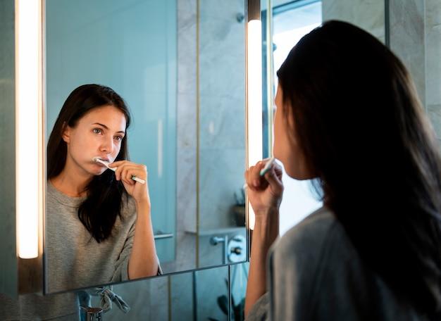 Женщина чистит зубы утром