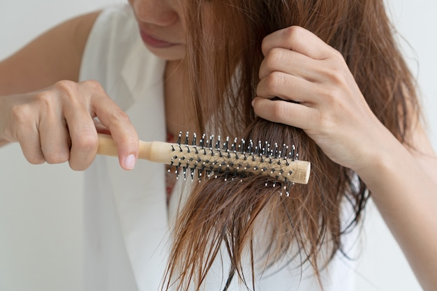 Woman brushing her wet messy hair after bath with comb, thin hair porblem. hair damage, health and beauty concept.