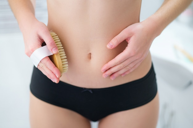 Woman brushing skin belly with a dry wooden brush to prevent and treatment cellulite skin and body problem.