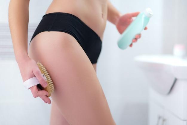 여자 화장실에서 샤워 후 셀룰 라이트와 신체 문제를 예방하고 치료하기 위해 마른 나무 브러시로 피부 엉덩이와 엉덩이를 칫솔질. 피부 건강