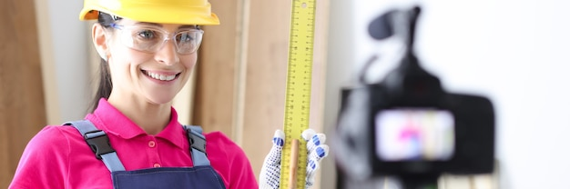 Woman builder demonstrates ruler on video camera