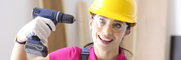 Woman builder in hard hat holds drill next to her head. all about diy repair and construction concept