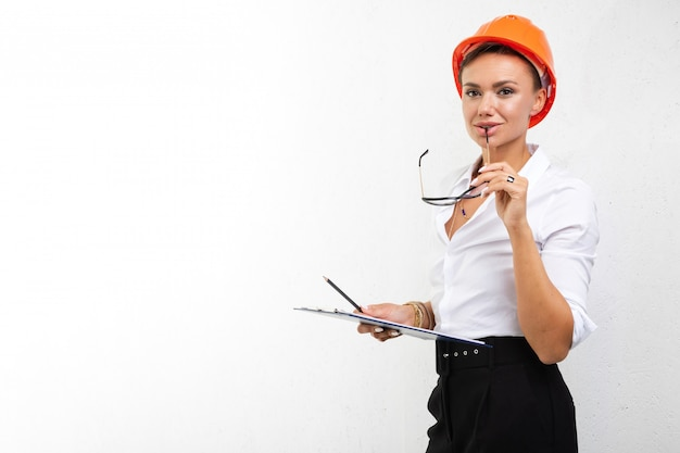 Woman builder in helmet on white isolated background