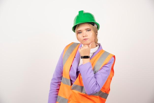 白い壁にヘルメットをかぶった女性ビルダー。