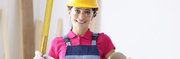 보호 헬멧과 고글 벽지와 눈금자를 들고있는 여자 작성기. 여성 개념에 대한 디자인 엔지니어 직업