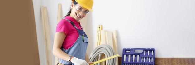 Женщина-строитель в защитном шлеме и комбинезоне держит в руках линейку