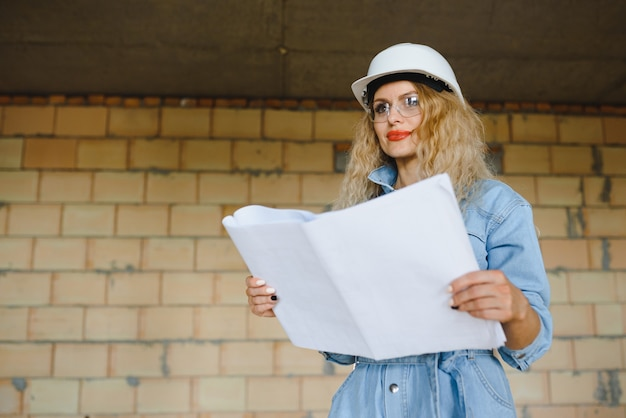 Woman builder looking at architectural blueprint in new apartment