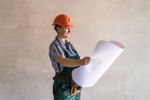 新しいアパートの建築設計図を見ている女性ビルダー