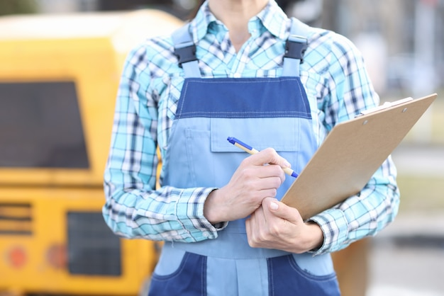 Woman builder in overalls holding clipboard and ballpoint pen closeup