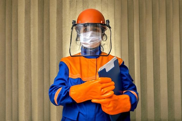 Женщина-строитель использует средства индивидуальной защиты и спецодежду или защитное снаряжение во время пандемии коронавирусной инфекции covid 19.