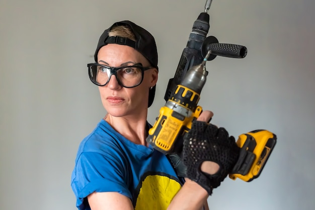 Строитель женщина с дрелью в руках для любых целей.