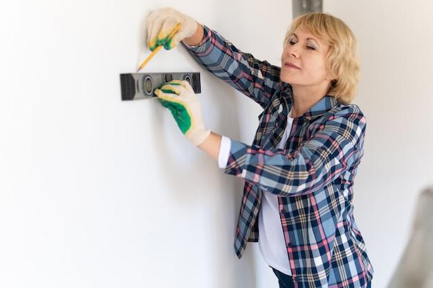 新しい建物で彼の手にレベルを持つ女性ビルダー。中年女性がアパートの修理をします。