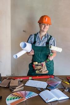 ロールと作業テーブルの青写真を持つ女性ビルダー