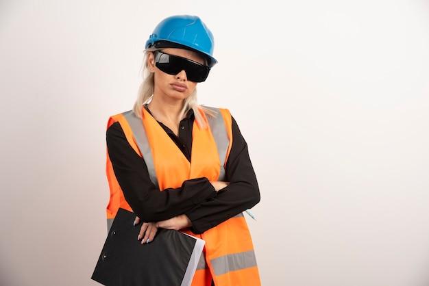 ゴーグルとクリップボードを持つ女性ビルダー。高品質の写真