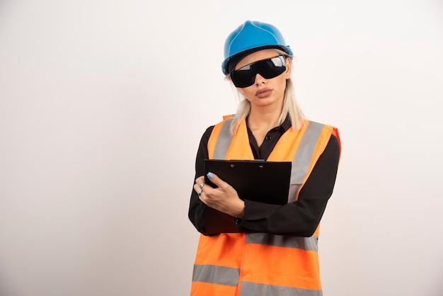 クリップボードを保持しているゴーグルを持つ女性ビルダー。高品質の写真