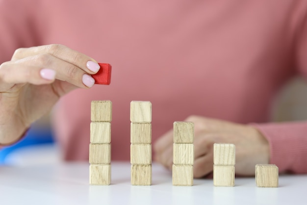 Woman building graph from wooden cubes closeup. profit growth concept
