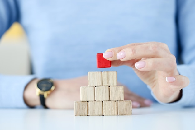 Woman building pyramid from wooden cubes closeup. leadership skill concept
