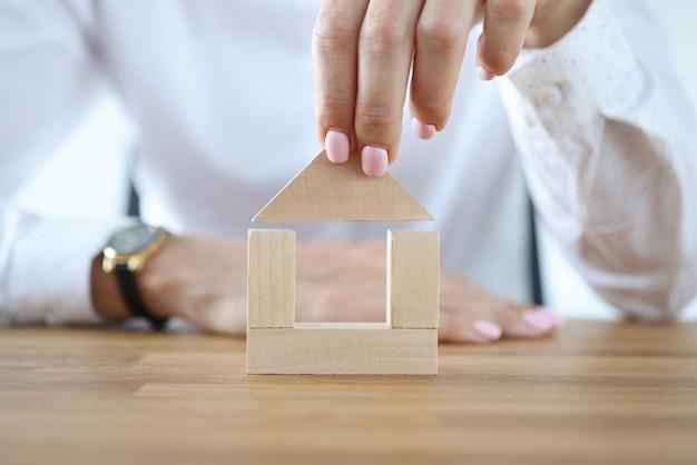 女性はテーブルの上の木製の立方体から家を建てます