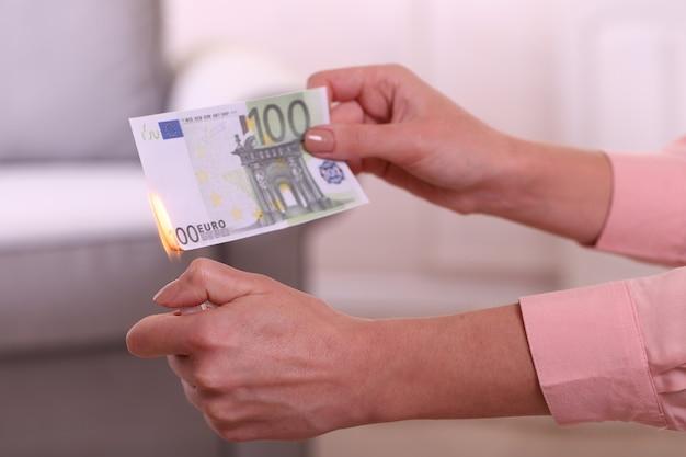 部屋でユーロを燃やす女性