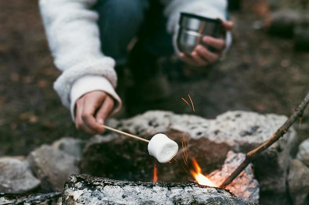 Donna che brucia marshmallow nel fuoco di campo